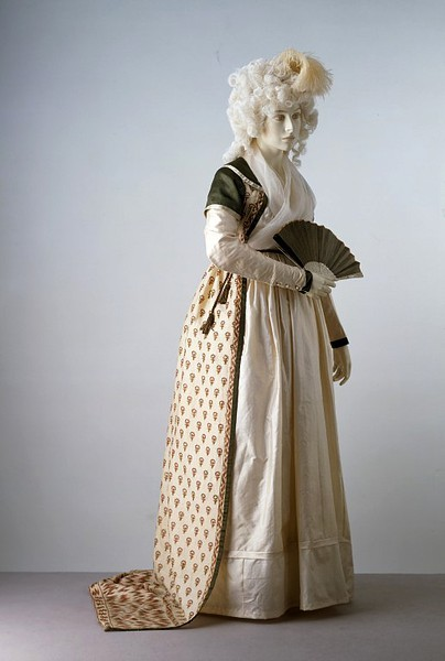 Robe, ca 1797 England, the Victoria & Albert Museum  Cashmere shawls were prized imports from India during the late 18th century. British manufacturers soon began making shawls in similar styles. Not only were they worn with the newly fashionable Neo-classical gowns, the shawls were also made into gowns. In this example of the late 1790s, the shawl was cut in half and then sewn together to form the front and back of the gown. Sleeves of cream satin and a collar and over-sleeves of green silk fabric were then added. The waistline is very high, sitting just below the bust line.