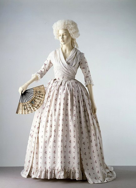 Afternoon dress, ca 1785 England, the Victoria & Albert Museum  In the 1770s and 1780s printed cotton fabrics began to replace silk in popularity for women's gowns. The material of this gown has a dotted ground and is printed in a repeating pattern of floral sprays. The gown has a fitted back and open front below the waist, revealing a petticoat of the same fabric. The lack of decoration and use of cotton instead of silk indicates that this gown was probably worn during summer afternoons for card games and tea parties, rather than for evening dress.