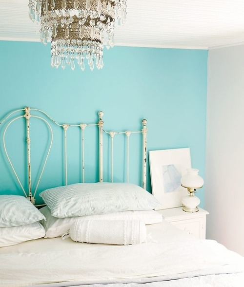 shabby bedroom with a beautiful chandelier and turquoise wall