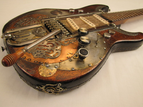 "Arkanacaster Guitar  by Tony Cochran Guitars   This electric guitar was the property of Country Western star Diamond Ted Raymond of Deadtree, Arkansas. He fitted it with what he called ""a harmonic deceptor"", a crude, but effective planking system that humanized bent notes. Diamond Ted specialized in a particularly nasty breed of Honky Tonk called Flinch Wailing. After it was outlawed by the state and condemned in the Catholic Telegraph, Diamond Ted went underground with his performances until his death in 1961. He passed out drunk while eating peanut butter with his hands, and squirrels ate his fingers off. He bled to death. Rumor has it … he wanted his guitar buried with him, but his lousy brother stole it from the funeral home. The deceptor doesn't seem to work anymore, but it's still a handsome piece."