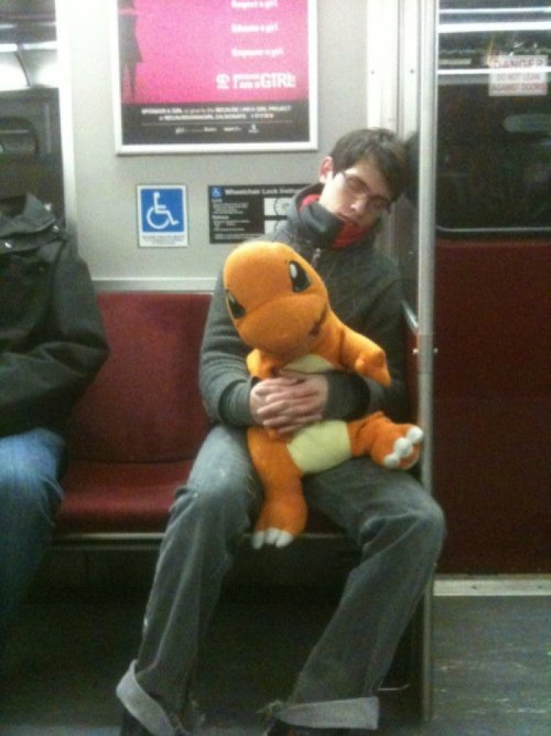 Guy Asleep on Train with Stuffed Charmander Got catch all the ZzZ's.