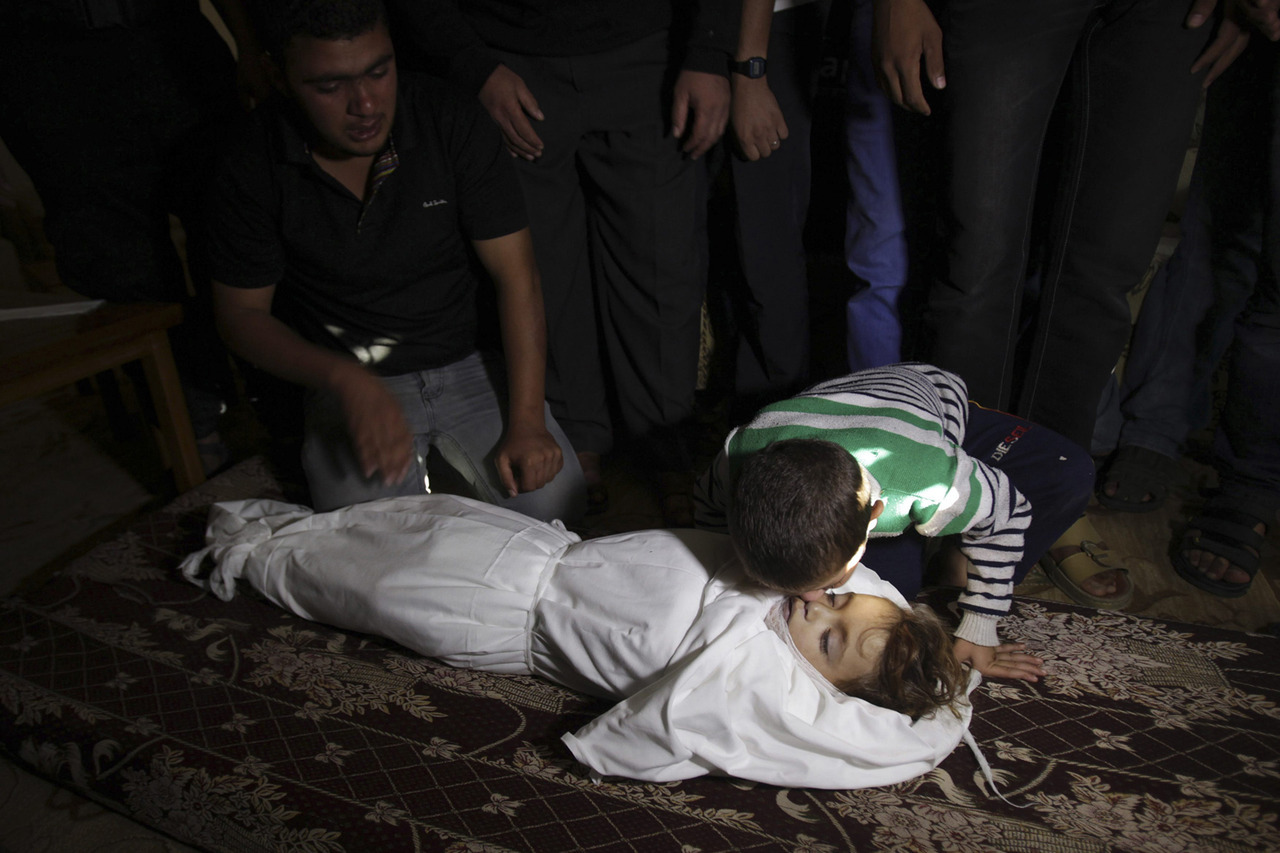 timelightbox:  Nov. 15, 2012. The brother of Palestinian boy Walid al-Abadlah, who according to hospital officials was killed in an Israeli air strike, kisses his body during his funeral in Khan Younis in the southern Gaza Strip. (photo: Ibraheem Abu Mustafa—Reuters) From escalating violence in the Gaza Strip and austerity riots in Europe to the flooding of Venice and murmurations of starlings in Scotland, TIME presents the best images of the week. See more photos here.