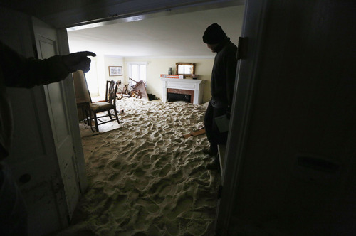 SURREAL ESTATE  A worker stands in a living room filled with sand two weeks after superstorm Sandy in Bay Head, New Jersey. (Photo: Mario Tama / Getty Images via The Guardian)