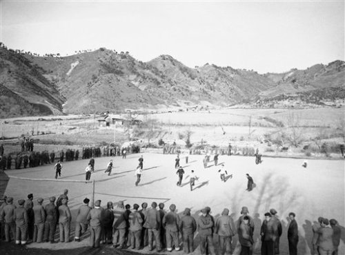 British prisoners of war play soccer, watched by other UN captives of the Reds in a camp at Chongsong, North Korea, Feb. 16, 1952. The picture was made by Frank Noel, Associated Press photographer and himself a prisoner. It was passed by both Red and UN censors. (AP Photo)