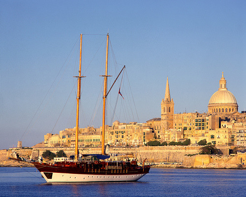 just-want-to-keep-on-living:  A boat, sailing opposite the city of Valletta, Malta.