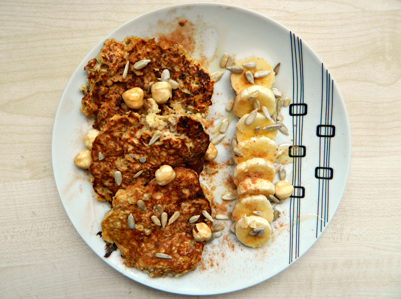 Banana-oat pancakes with cinnamon, hazelnuts, sunflower seeds, agave and the other half of the banana. I really fancied pancakes this morning but I didn't have any flour, so I made this mix up and they tasted wonderful! They're incredibly easy, cheap and it's likely you'll have these ingredients around the house anyway. Easily made gluten free! Ingredients/instructions -  1/2 cup oats, 1/2 a ripe banana (mashed), 1 egg, 2 or 3 tbsp soy yoghurt* and a few shakes of cinnamon. I simply mixed them all together, heated some coconut oil in a pan, poured the mix in to the pan in three sections and cooked away! Easy as pie. (or pancakes.) *I'm not sure if this is needed or not, I just added it to make the mix go further. Any yoghurt would work in place if you're good with dairy, or maybe a tiny dash of almond milk to thin it out, but not too much. If you do add too much milk, add some chias or flaxseed to thicken again. :)