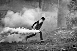 this-flesh:  A protester carries away a tear gas cannister during clashes with Egyptian riot policemen near Tahrir Square in Cairo, Egypt. November 2011.