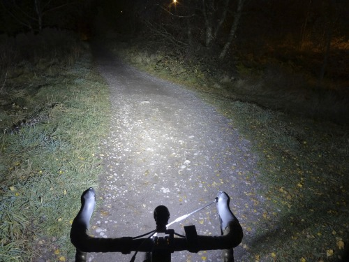 November 17th - Winter, cycling in darkness. I really can't stress this enough, but lights, folks, lights. Lights are about being seen - creating a moving point of highlight in a dark world. In an urban environment, that's all you need: to this end cheap LED blinkies and such are perfectly adequate. In rural environments, and for moving at speed off road in the dark, good forward illumination is essential. The better the light, the sooner you see hazards, the faster you can potentially go. I use an LED light by Hope, of Barnoldswick in the UK; it's their flagship R4 model, and is very bright indeed. This is a non-assisted photo and shows the light spread on a medium setting. I have a very bright rear light from the same company. I love Hope's stuff. They keep me safe at night.