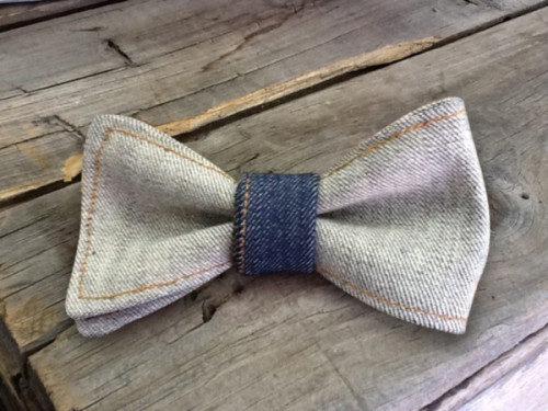 This American denim bow tie is crafted one at a time by hand in our workshop in downtown Los Angeles. Made from raw Cone Denim and has a denim weight of 9.5 oz.  All bow ties are stitched twice to ensure they last a long time in your wardrobe. Each bowtie comes with a den.m bar clip. Be the first in your group to rock this denim bow tie!  Material: Cone Denim Weight: 9.5 oz. Dimensions: 3 x 5 Type: Clip-On About den.m bar's Bow Ties for Men collection. All of our bow ties are crafted with the fine dapper in mind. We know you prize individuality, class & sophistication. We use only American and Japanese denim and stitch each bow tie on 1970's era Juki & Union Special sewing machines.