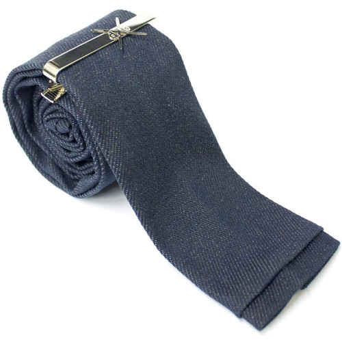 "This handcrafted denim skinny neck tie bridges modern & traditional and is made from Swift Denim based in Georgia. Swift Denim Mills has been around for 110 years! Our custom denim necktie are crafted one at a time and no two ties are exactly alike. Necktie measures 2"" at the widest length, 55"" long, and has a modern square tip. Necktie has a slight stretch to it and all of our neckties come with a custom den.m bar embossed tie clip. For the ultimate denim connoisseur, a denim necktie made in America from American denim.  Mill Origin: Swift Denim Mills  Weight: 12 oz. (medium weight denim) Dimensions: 2 x 55½ About den.m bar's Tie collection. All of our ties are crafted with the fine dapper in mind. We know you prize individuality, class & sophistication. We use only American and Japanese denim and stitch each tie on 1970's era Juki & Union Special sewing machines."