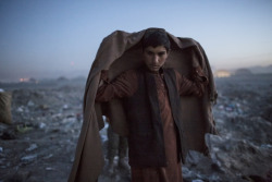 simply-war:  Nov. 14, 2012. An Afghan Pashtun boy, who said he was forced from the troubled province of Baglan due to threats from the Taliban, winds up his day after scavenging for recyclables at a garbage dump site in Kabul. Daniel Berehulak.