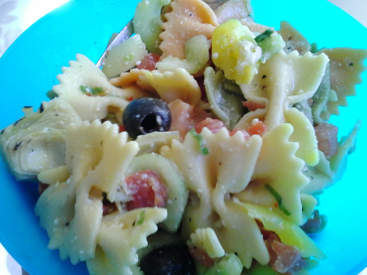 This is possibly the best pasta salad I've ever had, definitely the best I've ever made!! Vegetable rainbow bow ties, 4 medium tomatoes, 1 large cucumber, olives, grilled artichoke hearts from the jar, pepper rings, green onion, good seasons Italian dressing mix, and grated romano  :-D