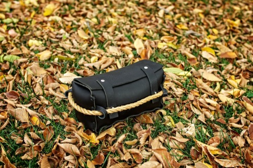 "HF Triple: An Awesome Stuff Bag now available in Water Buffalo Flat Black. While antique adventuring (you know, like Indiana Jones) HF designer Matt Swaggart discovered an heirloom rope that inspired this rugged dopp kit. Designed with just enough space for essentials (10x4.5x4.5), this personal duffel gets its ""Triple"" name from its unique form that allows the holder to grip the bag from three sides.  No cookie cutters here. Each one-of-a-kind bag is handcrafted by Swaggart himself from durable, high-grade, Kodiak oil-tanned cowhide. And the detailing is exquisite—pronounced leather grain, rugged coloring, a pressed logo-strap that secures key contents inside, and of course the antique rope. Each edition comes when (and only when) Swaggart makes his next great antique rope discovery. More Info Here"