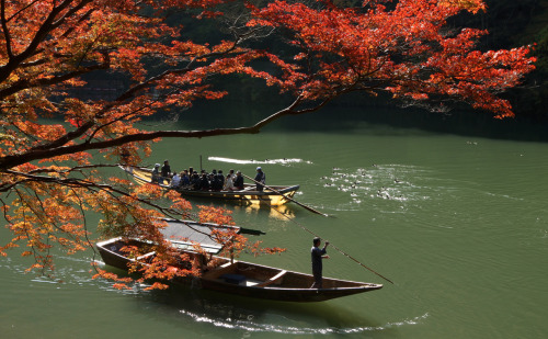 gettyimages:  Autumn Colors In Kyoto A man ferries tourists under maple trees on the Katsura river in Arashiyama on November 19, 2012 in Kyoto, Japan. Thousands of tourist come to enjoy the autumn colors of the maple leaves every year. Photo by Buddhika Weerasinghe/Getty Images