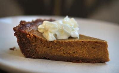 Pumpkin Pie With Gingersnap Crust  Yield: 8 to 12 servings Time: 1¼ to 1½ hours, mostly unattended ¼ cup (½ stick) unsalted butter 8 ounces gingersnaps (about 3 cups) 1 tablespoon all-purpose flour ¾ cup plus 1 tablespoon sugar 2 large eggs One 15-ounce can pumpkin purée ¾ cup half-and-half 1½ teaspoons ground cinnamon 1 teaspoon ground ginger ½ teaspoon salt Pinch ground nutmeg Pinch ground allspice Pinch ground cloves 1. Heat the oven to 350°F. Melt the butter in a small saucepan over low heat (or in a small bowl in the microwave). Break up the gingersnaps slightly; put them in a food processor and pulse until they are finely ground. Add the butter, flour, and 1 tablespoon of the sugar. Pulse a few times to combine. Press the gingersnap mixture evenly into the bottom and sides of a 9-inch pie pan, and bake for 5 minutes. 2. Beat the eggs in a large bowl. Whisk in the remaining ¾ cup sugar and the pumpkin, half-and-half, cinnamon, ginger, salt, nutmeg, allspice, and cloves. Transfer the pumpkin mixture to the crust, and bake at 350°F until a knife inserted into the center of the pie comes out clean, about 1 hour. (The center of the pie will not be completely firm.) Cool thoroughly. Serve at room temperature, or cover with foil or plastic wrap and refrigerate for up to a day before serving. (Store leftover pumpkin pie covered with foil or plastic wrap in the refrigerator for up to several days.)  (via Pumpkin pie with gingersnap crust: A vast improvement over pâte brisée.)