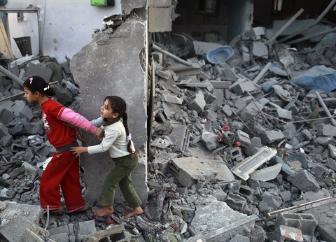 "newshour:  Palestinian girls run away after an Israeli air strike on a house in the northern Gaza Strip on Nov. 18. Photo by Mohammed Salem/Reuters. In Gaza, there are no sirens, no warnings and no bomb shelters. ""We put plastic on the glass so that if it's shattered during an air strike we won't get hurt,"" 35-year-old Marwa Bahar relays by telephone. ""We run out to get supplies — bread, gasoline for generators and water — whenever we can. During bombing it's safer in the apartment stairwell but nowhere is really safe."" A colleague told me about the Almadhun family — four of the five family members are deaf. There's no electricity in Gaza so they have no way of receiving television cues or audio warnings of any sort when air and naval strikes are ongoing. ""We also stay together. My sister lives on the 10th floor and now she has move into our place on the second floor,"" added Bahar. ""If people live in different parts of the city, they stay together in one place. It helps with support. If anything, this situation makes people more committed to Hamas."" His face smeared with soot and white dust coating his black T-shirt , 30-year-old Ahmed Saleh stands atop the rubble that had been his home a day before. ""It was morning and we were sleeping. The walls collapsed. We didn't understand what was happening and we couldn't find the children. We had to dig them out. They were buried underneath the rubble."" The irony is that as European, U.N., U.S., Egyptian and Arab League leaders work overtime to hammer out a ceasefire deal, Hamas, Islamic Jihad and Israel continue pounding each other. And the death toll is mounting in Gaza."