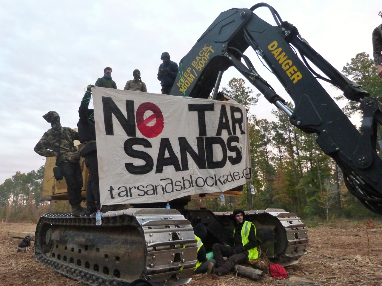 Here's just a preview of the Tar Sands Blockade mass action to stop the Keystone XL pipeline today in Nacogdoches, Texas: Four blockaders locked themselves down to construction and land clearing equipment early this morning. Two blockaders were pepper-sprayed, all four were arrested and two direct support comrades were also arrested. Police used excessive force, especially when removing protesters from the land. Officers also refused to wipe the faces of the two blockaders who were pepper sprayed, leaving them covered in painful chemicals. They were all also refused water onsite. All six were released a couple of hours later. In an attempt to stop the cherry picker from extracting three tree-sitters, a swarm of protesters stood in the road to prevent the machine's passing. A police officer immediately defended the machinery and pepper-sprayed the crowd without warning, striking a 75-year-old woman, a Nacogdoches resident and others at point blank. Two were arrested for blocking the road. Another comrade was also arrested at the tree-sit site. Three tree-sitters (photos of this awesome protest coming soon) were extracted from their platforms by a cherry picker this afternoon. They were all arrested, two were strip searched and all tree-sitters are still in jail. The charges against them are still unknown. Earlier in the day, east Texas residents and Tar Sands Blockade supporters held a rally in solidarity with the blockaders & tree-sitters. Solidarity actions were held in more than 40 cities worldwide.  Click here if you want to donate to help Tar Sands Blockade continue their great work! More details & tons of photos coming soon, so stay tuned.