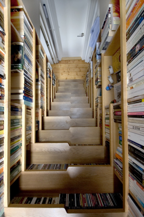 persentisco:  Book-lined staircase by Levitate Architects.  Made of english oak shelving, this is an ingenious solution to a book storage problem. It not only stores books but this piece actually extended its London flat into the unused loft space above it, creating a new bedroom level and increasing the floor area of the flat by approximately one third. The staircase is hidden from the main reception area of the loft and a skylight and roof lights, light the new bedroom above.