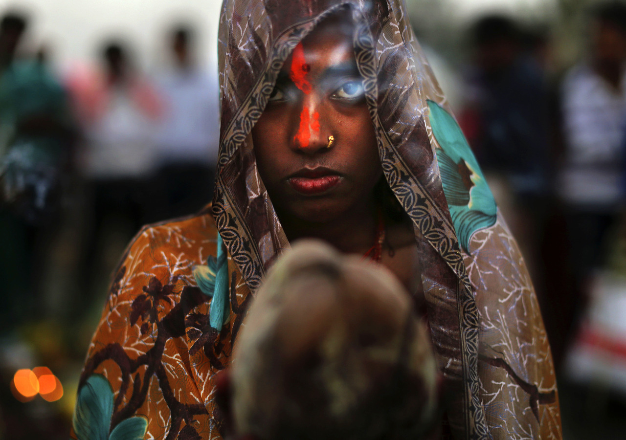 Pray. Incense smoke wafts past the face of an Indian Hindu devotee as she prays as part of rituals at sunset in the holy Yamuna River during the Chhath Puja festival in New Delhi. Chhath prayers, an ancient Hindu festival popular amongst the working class, is performed to thank the Sun God for sustaining life on earth. Prière. Une volute d'encens flotte devant le visage  de ce jeune Hindou alors qu'il prie dans la rivière sacrée Yamuna durant le coucher de soleil. Ce rituel sacré fait partie intégrante du festival Chhath Puja de New Delhi. Ce festival indou antique est populaire parmi la classe ouvrière. Cette prière Chhath est exécutées pour remercier le Dieu du Soleil de perpétrer la vie sur terre.  PHOTOGRAPHER : AP PHOTO/KEVIN FRAYER