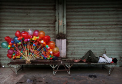 A balloon seller sleeping next to his wares in New Delhi » Kevin Frayer, via NYT