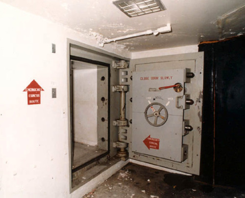 NASA's Rubber Room Image: Top: The door to the rubber room. Middle: The rubber room with fire blankets in the center. Credit: NASA  The Saturn V was huge, and huge rockets tend to have proportionately devastating explosions. Engineers calculated that a Saturn V exploding on the launch pad would turn into a fireball 1,408 feet (430 meters) wide and burn for nearly 40 seconds reaching a peak temperature of 2,500 degrees Fahrenheit (1,380 degrees Celsius).  In the age of Saturn V — the 60s and 70s — to get astronauts and launch crews clear of a fatal explosion, NASA had three possible escape plans in place: the launch escape system that would pull the command module free from the rocket during an abort; a slide wire astronauts could ride to a safe point on the ground; and an underground blast chamber.  The blast chamber is somehow buried in all the Apollo-era history. It's fitting, perhaps, since it's actually directly beneath the launch pad where the theoretical Saturn V explosion would have occurred.  The blast room is basically a bomb shelter. A small, circular room, it's mounted on massive springs like a missile silo. This means that anyone inside would feel little disturbance when the Saturn V exploded right overhead.  Lining the room are huge chairs, big enough for an astronaut in a full pressure suit to strap himself in for safety. There's also one fire blanket per man in the center of the room (shown below).  Up to 20 men could seek refuge in the blast chamber for up to 24 hours, though with more men, things became problematic due to the rise in carbon dioxide levels. The room was equipped with carbon dioxide scrubbers that came with spare filters and a store of oxygen candles — a type of chemical oxygen generator containing a mix of sodium chlorate and iron powder that burns to produce 6.5 man-hours of oxygen per kilogram of the gas mixture.  At the time, on the wall was a detailed schedule outlining exactly when oxygen candles had to be lit and filters had to be changed. With less than six men in the blast room, they could all breathe normally for a full day while the air above them cleared. With up to 10 men in the room, things got a little more complicated. Additional methods of providing oxygen became imperative if everyone inside was going to survive.  As evidence that men could last for a while in the blast room, there was even a toilet. But barely tucked away behind one of the chairs, using it in such a small space wouldn't have been an appealing prospect.  To get into this fortress of safety, the astronauts and pad crews had to take a ride. Elevators would carry them from any level on the gantry to the base of the mobile launch platform where, on the north side, was a square door with rounded edges. It opened to a slide, 200 feet (60 meters) long, that would send astronauts and pad crews on a winding ride to a point 40 feet (12 meters) under the launch pad. They landed in the rubber room, so called because it was padded entirely with bouncy rubber. A six inch steel door admitted them through a short tunnel and into the blast chamber.  Once the air around the launch pad had cleared and it was safe to leave, astronauts and pad crews could take one of two long, narrow, and winding tunnels to the western edge of the launch pad area. There, they could open a door and step outside.  After the Apollo program ended, the rubber rooms and blast chambers were abandoned in place. There were no circumstances under which shuttle astronauts would use this underground shelter; the preferred method beginning in the 1980s were the gondolas on cables that led from the top of the gantry to a safe site on the ground.  The rubber room and blast chamber, at least the one under Pad A, is still there. It's off limits to the public and preserved as a historic site, but if you can finagle your way in (which involves knowing the right people) it's definitely a piece of history worth seeing.  To see NASA's rubber room in all its glory, watch a clip from a BBC documentary on the Apollo emergency escape procedure.