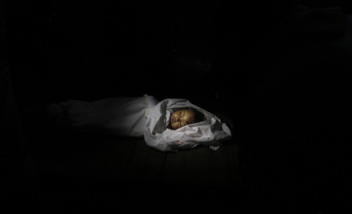 """The body of 10-month-old Palestinian infant Haneen Tafesh lies in the morgue of Shifa hospital in Gaza City, on November 15, 2012."" (AP Photo/Hatem Moussa)"