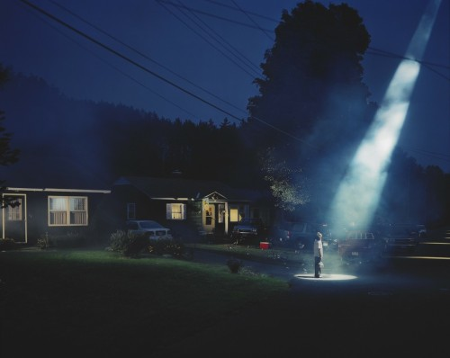 "cavetocanvas:  Gregory Crewdson, Untitled, 1998 From the Indianapolis Museum of Art:  A solitary man stands in a dark driveway holding a six-pack of beer, spellbound by a shaft of light. Gregory Crewdson has carefully composed each detail in this photograph, part of his series ""Twilight,"" in which various residents of an anonymous town are transfixed by seemingly paranormal forces at dusk. Citing the films of Stephen Spielberg and David Lynch as influences, Crewdson acts as director to actors and a full production crew. His elaborate process results in a single picture, which he refers to as a ""single-frame movie."" Here, small-town America is depicted as both familiar and strange, threatening and miraculous."