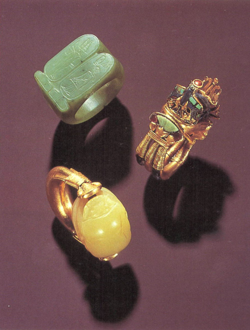 soularbloom:  Three of Tutankhamun's Rings (a) The green nephrite signet shows the King and Min.(b) The three-dimensional bezel is formed from a lapis lazuli scarab flanked by an inlaid falcon and moon barque on a cartouche-shaped base. The inlays are green jasper and glass.(c) The scarab bezel of the gold ring is of chalcedony; the underside shows Thoth and the udjat.