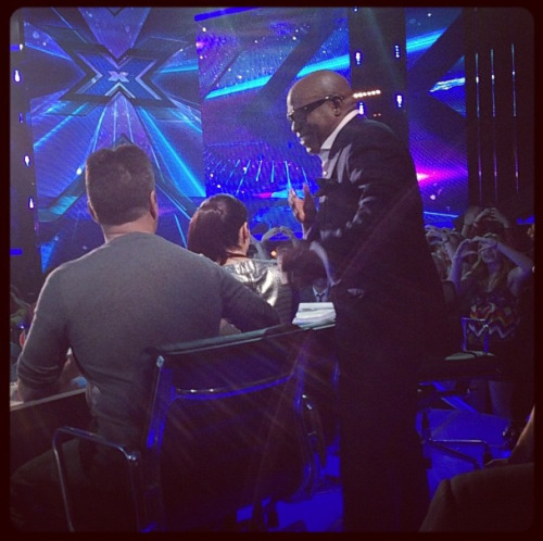 While LA Reid talks to Simon Cowell, Demi gives hearts to the audience!