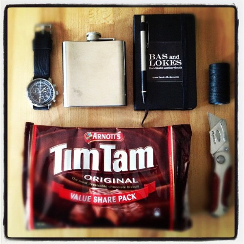"Today's very essential carry at the office. Lots of #timtam    chocolate a #flask of stuff with high alcohol content, keeping the time with a pilot watch on our ""Joel"" handmade leather #watchstrap a #moleskine full of things to do and cross out and lots of cutting and sewing today. Happy holidays, people! #wruw #womw #timepiece"