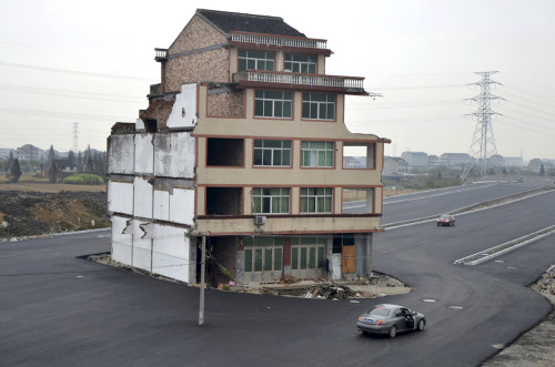 guardian:  An extraordinary picture of a house in the middle of a newly built road in Wenling, Zhejiang province, China. An elderly couple refused to sign an agreement to allow their house to be demolished. They say that compensation offered is not enough to cover rebuilding costs. This and all the best news images from Thursday here: Photograph: China Daily/Reuters  Don't be surprised if this image becomes iconic among U.S. opponents of eminent domain.