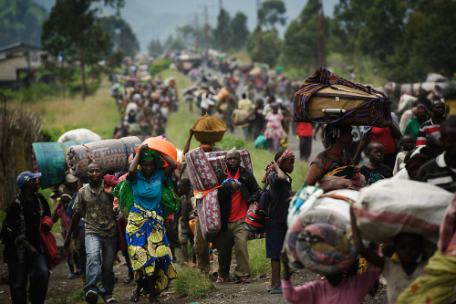 fotojournalismus:  Thousands of Congolese flee the town of Sake, 26km west of Goma, following fresh fighting in the eastern Democratic Republic of the Congo town on November 22, 2012. The rebel militia M23 – widely believed to be backed by Rwanda – holds the major city of Goma but was taken by surprise on Thursday in the village of Sake, 26km away, when government soldiers launched a counter-offensive, opening fire from surrounding hills. A humanitarian crisis is looming in eastern Democratic Republic of the Congo, aid agencies have warned, after another day of fighting sent thousands of people fleeing for safety.  [Credit : Phil Moore/AFP/Getty Images]
