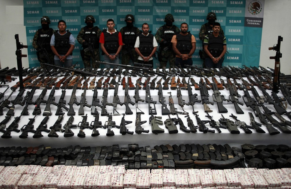 drugwar:  Suspects are lined up as weapons are displayed to the media by the Mexican Navy in Mexico City June 9, 2011. According to the Mexican Navy, 204 rifles, 11 guns, 15 hand grenades, uniforms of the Mexican navy and of the U.S. army, over 29,000 cartridges and over 200 kg (441 pounds) of cocaine and were seized in an operation against the Zetas drug cartel in Coahuila and Nuevo Leon in the north of Mexico.