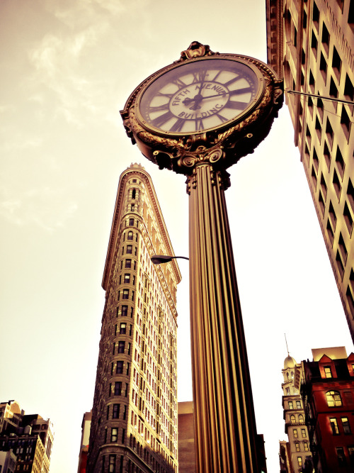 "The Flatiron Building and Fifth Avenue Building Clock. Midtown.  I have always loved the ornate clocks that line 5th Avenue, especially the Fifth Avenue Building Block that has a prime destination near the Flatiron Building. At 19 feet high, the cast-iron clock was installed in 1909 and was crafted by a Brooklyn Iron Works company. It's a type of clock that was introduced in the 1860s. They were popular with business owners who wanted to attract extra attention and also served a functional purpose as time-telling pieces in a busy area of Manhattan.  The juxtaposition between the Flatiron Building, one of New York City's iconic skyscrapers and this cast-iron clock has always put a smile on my face. The Flatiron Building, which was completed in 1902 is also a landmark in Manhattan. Its name is in reference to its resemblance to a cast-iron clothes iron.    —-  View this photo larger and on black on my Google Plus page  —-  Buy ""Flatiron Building and 5th Avenue Building Clock - New York City"" Prints here, email me, or ask for help."