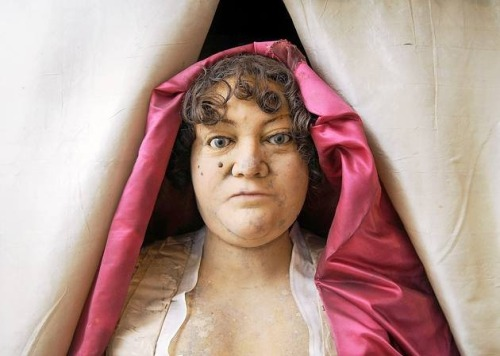 "theoddmentemporium:  The Wax Effigy of Sarah Hare Sarah Hare died in 1744 at the age of 55 of a commonplace accident. It was said that she ""used to sew on a Sunday and as a punishment died from pricking her finger. "" Sarah did indeed die after injuring herself while sewing, likely, from septicemia. [She] made no extraordinary contributions to this world except one – a wax effigy of herself, the only such mortuary statue of its kind in England outside of Westminster Abbey [See Also].  Today we know very little about Hare's life except that she never married and was not very pretty. In a will dated August 1743, Sarah made a series of curious requests:  ""This I hope my Executor will see firstly performed before Sunset … I desire to have my face and hands made in wax with a piece of crimson satin thrown like a garment in a picture hair upon my head and put in a case of Mahogany with a glass before and fix'd up so near the place were my corps lyes as it can be with my name and time of Death put upon the case in any manner most desirable if I do not execute this in my life I desire it may be done after my Death.""  Her wishes were met … molded impressions were made of her face and hands, which were poured in wax. She was buried in the Hare mausoleum in Holy Trinity church. Surrounding her closed mahogany cabinet, which is situated in a corner of the vault, are memorials to the Hare family, dating from the 17th-20th centuries. Her cabinet is plain. A bronze plate engraved with the words – ""Here lyeth the body of Sarah Hare…"" – its only adornment. Her lifesize effigy has waited for over 250 years behind a pair of mahogany doors for the occasional visitor to find it."