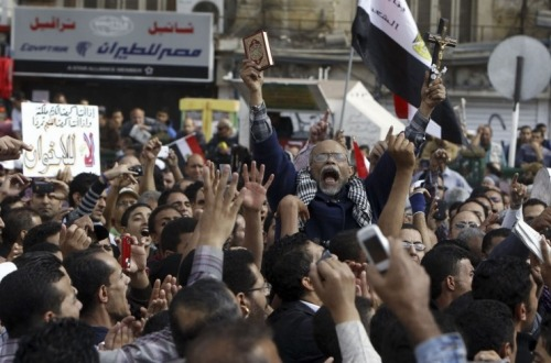 shortformblog:  A year after Hosni Mubarak's fall, new round of protests in Egypt: Tear gas filled the streets and 15 were injured in protests after President Mohammed Morsi issued a decree yesterday greatly expanding his own power. The decree shields any of the president's decisions from legal challenge until a new parliament is elected; protects the Islamist-dominated assembly, which is in the process of crafting a new constitution for the country, from being dissolved; and calls for retrials of Hosni Mubarak and other members of the old guard. 18 liberal and Christain members of the aforementioned assembly recently withdrew from the process, claiming that their input wasn't being addressed; Morsi's claims that his decree will only be in effect until the new constitution is drafted. Both pro- and anti-Morsi protesters clashed in Egyptian streets today, numbering in the thousands. source [1] [2] [3] (Photo credit: Reuters)
