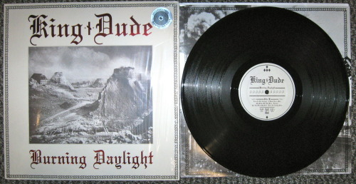 "King Dude - ""Burning Daylight"" (Dais Records 2012) I so rarely get excited for new music coming out anymore.  It's not that I'm a jaded old fuck that doesn't listen to new music; far from it, probably 85% of the music I buy would have come out in the last 3 or 4 years.  I get excited when I discover a new band or artist that really blows my mind.  It's rare, but it does happen to me on occasion.  Sadly once and artist or album blows my mind, I kind of forget about them and move on to something else.  Last year around this time, King Dude's ""Love"" came out, and I was completely enthralled by it.  I have been slowly tracking down every one of his records ever since, and When I heard this was coming out, I couldn't pre-order it fast enough.   This came out about a month ago, but I'm finally getting to listen to it, and boy-howdy, it doesn't disappoint. You'll read all over the internet, from lazy reviewers mostly, that this is a neo-folk album, but that description couldn't be more wrong.  While King Dude is obviously influenced by neo-folk, this is totally an American folk album.  King Dude, uses the tricks of the neo-folk trade like heavily reverbed vocals, atypical percussion, and pagan/occult symbolism, and creates something that is wholly unique and fresh.  Think if your favorite baritone country singer (Johnny Cash, because let's be honest, he's everyone's favorite baritone country singer) decided that he really likes current Death In June and his contemporaries, but likes doo wop, surf, and classic American folk even more, and King Dude is what you would get.  Also that what I like about him, is that none of this feels pretentious, because you can tell King Dude is doing this for fun, just to make some good tunes.  I wish more people knew about this guy.  I feel like his music is something that goths, punks, rockabilly dudes, and any other wierd music subculture could get into.   Seriously though, this album is leaps and bounds better than ""Love"", This will probably fall into one of my favorite albums of all time, it's that fucking good.  You all need to experience this now.   -Log."