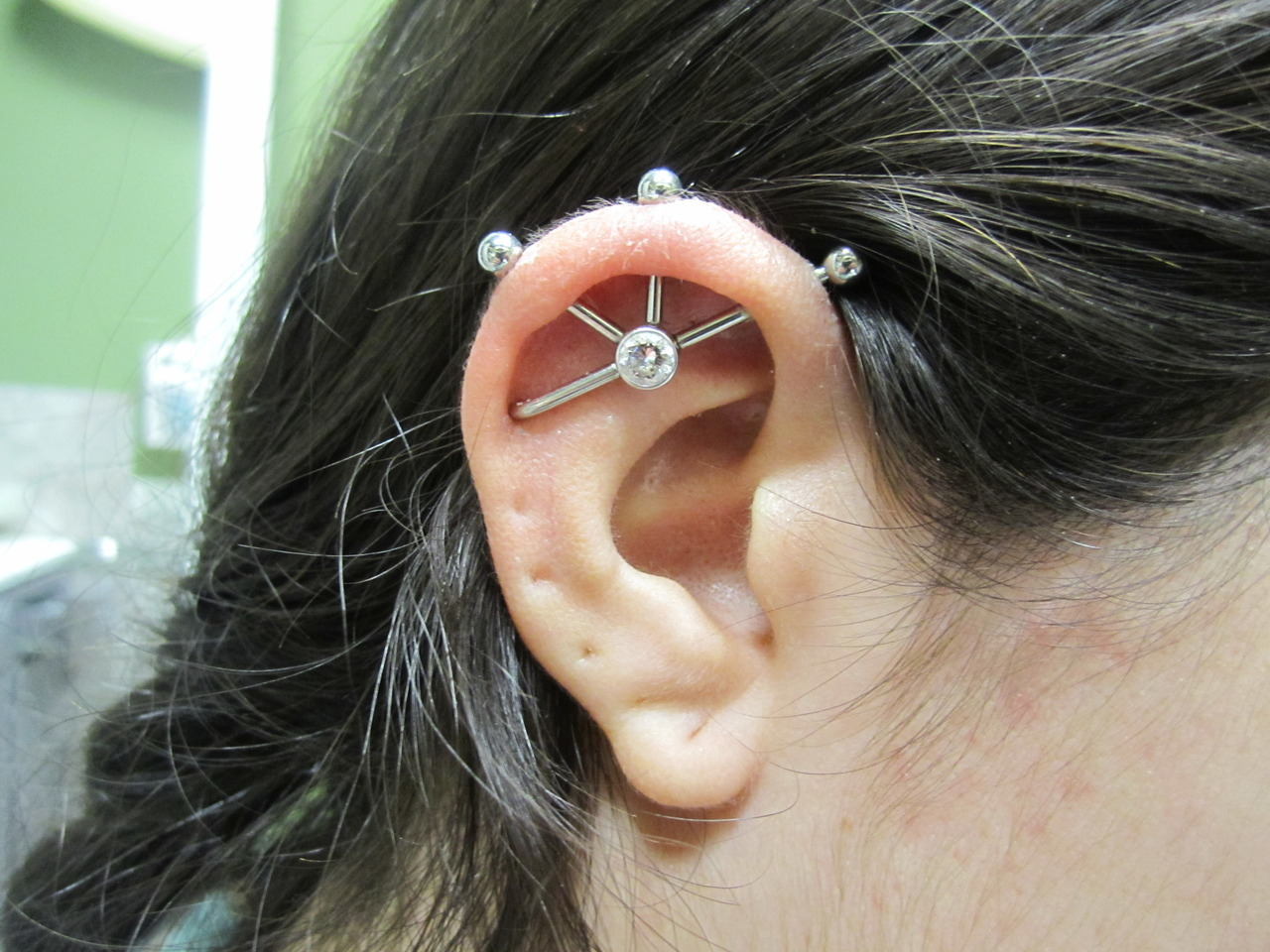 Custom 14k white gold quad threaded center. All healed and done with this piece initially.