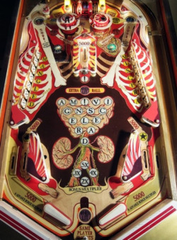 "wnycradiolab:  moshita:  pinball machine  Howie Tsui  From the article:  The artist — recent winner of the $5,000 emerging artist award from the Council of the Arts in Ottawa — was asked by a gallery to create works for an exhibition on the bicentennial of War of 1812, with a theme on the health-care side of battle. Tsui was skeptical, but research taught him that battlefield surgery ""was a really messy procedure,"" he tells me during an interview in his Centretown home. ""Since a musket (ball) isn't aerodynamic, when it enters your body it doesn't come clean out, like a modern bullet, it just kind of rattles around in your torso."" Others might imagine that ball rattling around their innards and think ""ouch."" What Tsui thought was, ""it's kind of like a pinball machine."" His art project on historic military health-care was born.  I'd very much like to hear the sound effects on this game.  I want this!!!"