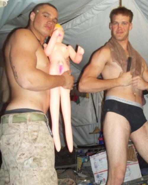 A couple of army buddies, stripping down to their briefs,  to have some fun with a blow up doll in a barrack tent.
