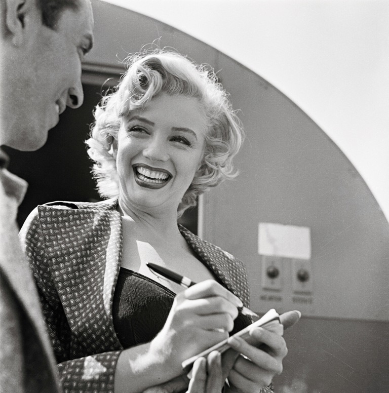 Marilyn Monroe signing an autograph for a fan, 1952.