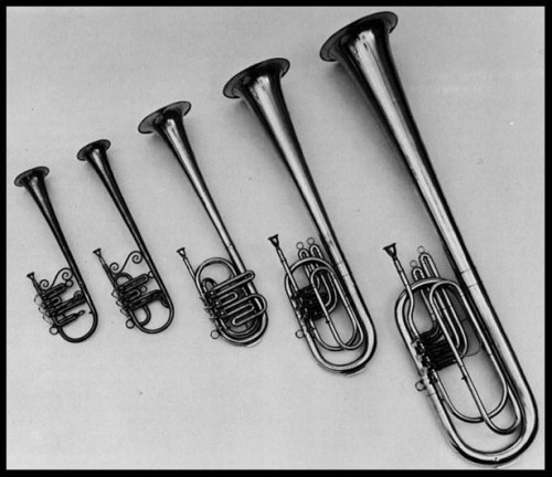 "Set of over-the-shoulder saxhorns from the collections of the Smithsonian Institution, Division of Musical Instruments. From left to right: E-flat soprano saxhorn, B-flat contralto saxhorn, E-flat tenor horn, B-flat bass (baritone), and E-flat bass (tuba). The cornets and saxhorns made up the all-brass bands of the 1850s and remained a popular, though decreasingly prominent, feature of American wind bands hrough the nineteenth century. The leading E-flat soprano part usually demanded extraordinary virtuosity, and the prominent role played by the E-flat cornet or soprano saxhorn-Flügelhorn-type instruments is characteristic of early American brass band music. At the same time, the uniquely homogeneous and mellow sound created by the whole family of horns ranging from soprano to bass is the outstanding quality of these instruments. All the instruments illustrated here bear the name ""J. Howard Foote"" but may have been manufactured by John Stratton. Foote and Stratton were partners for two years (1864-65), and Foote appears to have been a dealer rather than a maker. Stratton was an entrepreneur of first rank. He himself claimed to have developed the first plant for the mass production of brass instruments, and at a most propitious time. Just before the Civil War, he recognized the market for band instruments that could be delivered immediately and were not made to order. The war and the great number of instruments required by the Union Army made him and his New York factory a great success."