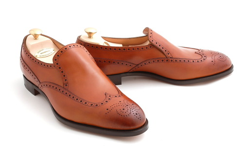 Edward Green. It's unusual to see a brogued shoe like this without laces. But this marries the loafer and brogue aesthetics beautifully together on a luggage-brown vegetable tanned leather. I love the burnished toe, too.  If you're not familiar with the English brand Edward Green, but are a fan of beautiful men's shoes, go here and enjoy the wonder.
