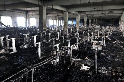 inothernews:  A fire inside a multi-story garment factory outside Dhaka, Bangladesh killed at least 111 people.  Most of the workers inside the building died on the first and second floors, where there were not enough exits — and those that did exist did not open to the outside.  Bangladesh is the second largest clothes exporter after China, and has a notorious safety record; more than 500 workers have died in factory fires there since 2006.  (Photo: Abir Abdullah / EPA via The New York Times)  The factory stricken by this deadly fire was producing clothing for Tazreen Fashion Ltd., which was sold, among other places, at Switzerland's discount C&A chain.