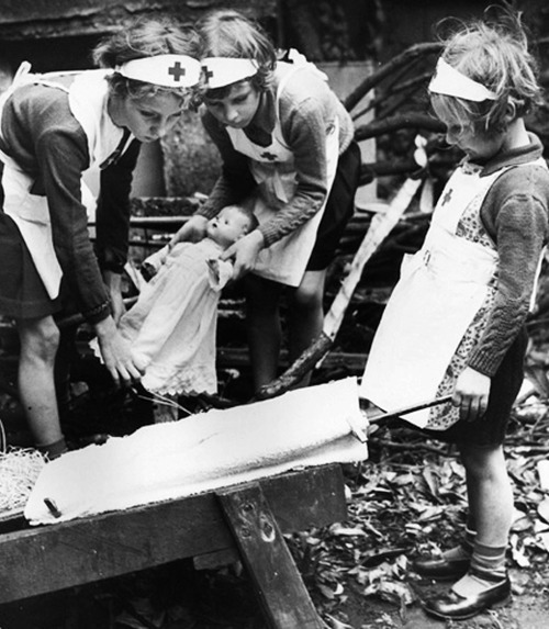 artsexsurvival:  Children pretend to be nurses in the ruins of a bombed London, WWII.