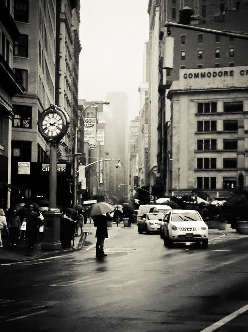 "nythroughthelens:  New York City in the rain. Flatiron District, Midtown. There is an inherent romance that buzzes through the air in New York City when it rains. The Flatiron District is one of my favorite areas in Manhattan when it rains. The street (5th Avenue) opens up to reveal distant skyscrapers that disappear into heavy fog as people weave their way through the multitudes of umbrellas. The clock in this image is the Fifth Avenue Building Clock (a close-up image and its history is in this post) which is a New York City landmark and recalls another era: one where these ornamental clocks played a role in attracting people to gilded era storefronts. This vantage point is with the Flatiron Building directly in back of the viewer looking up 5th Avenue. —- I have had quite a few requests that I add some of my New York City mobile photography to my online store and portfolio since people are looking to buy holiday gifts. This is the first of one of those requests. It was taken with my phone and has been lovingly added (link below!). —- View this photo larger and on black on my Google Plus page —- Buy ""New York City - Rain"" Prints here, email me, or ask for help."