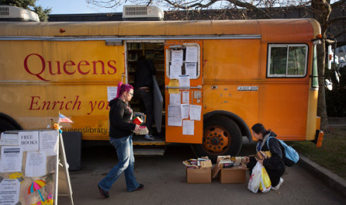 """Still There for Them"": Post-Sandy Libraries and the Permanence of Mobility The New York Times has a story today about how the Queens Borough Public Library is adapting its services to the Rockaways after the devastation wrought by Sandy:  The Rockaways still look like ghost towns. But the community libraries are there — if only in the form of a bus, parked in front of the gutted, muddy Peninsula branch. Days after the storm laid waste to four Queens Borough Public Library branches in the Rockaways, a colorful mobile library bus has hummed just outside its former location on Rockaway Beach Boulevard, offering warmth, power outlets, emergency information and books.  It is clear that this reliability, as much as the services themselves, have been crucial for residents whose everyday lives are now marked by a sort of messy, difficult uncertainty. ""The library is consistent — it's in the category of post office,"" one resident told the Times. ""So it's comforting that the library is functioning and open."" And when Christian Zabriskie, with Urban Librarians Unite, wrote up the Queens post-Sandy mobile program for the LibraryLab at Boing Boing, he, too, emphasized constancy and presence:  These are all the direct benefits, but there are many intangibles as well. Everyone knew that, even at their lowest point, the library was still there for them. Some volunteer librarians from Queens were able to do a storytime at a relief distribution point. It's strange to tell stories in the open air, with children sitting on matteresses in the dirt, while their parents scramble for food and blankets around you—and incredibly inspiring. It was a moment of normalcy, of comfort, of safety.  There's a fantastic, touching irony to the fact that what offers this consistency, this reliable and continued service, is a bookmobile, the very point of which is, largely at least, its mobility. The library can remain present because the bookmobile isn't stationary. Its impermanence has made it more reliable that bricks and mortar. (This isn't, by the way, the first time the Queens Borough Public Library has used bookmobiles to respond to change—though that change has tended to be social, not natural. As I wrote about almost exactly a year ago, the library used a bookmobile in the late 1960s to reach African American teenagers and take part in the rapidly shifting politics of the moment.) Photo from the New York Times"