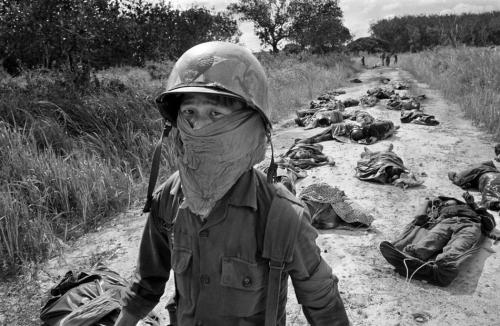 In this Nov. 27, 1965 photo, a Vietnamese litter bearer wears a face mask to keep out the smell as he passes the bodies of U.S. and Vietnamese soldiers killed in fighting against the Viet Cong at the Michelin rubber plantation, about 45 miles northeast of Saigon. (AP Photo/Horst Faas, File)