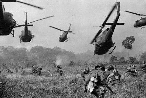 In this March 1965 photo, hovering U.S. Army helicopters pour machine gun fire into the tree line to cover the advance of South Vietnamese ground troops in an attack on a Viet Cong camp 18 miles north of Tay Ninh, Vietnam, northwest of Saigon near the Cambodian border. (AP Photo/Horst Faas)
