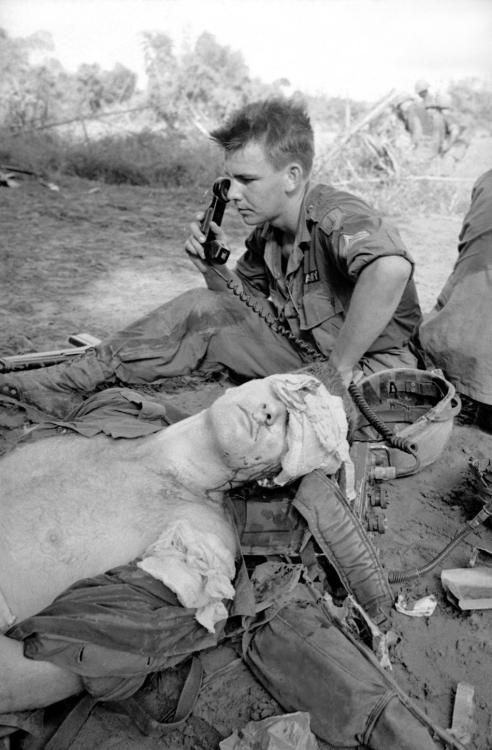 Seriously injured by shrapnel grenades planted in a booby trapped Viet Cong propaganda stall, a U.S. soldier awaits evacuation from Vietnamese jungle by ambulance helicopter being summoned by a radio operator behind him on Dec. 5, 1965. The soldier was attempting to tear down a Viet Cong bamboo structure used to dispense propaganda when two M 79 grenades planted in one of the poles exploded in his face. (AP Photo/Horst Faas)